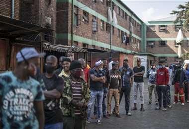 Hombres se alinean para que le hagan la prueba del Covid-19 en un albergue de Johannesburgo (Sudáfrica). Foto AFP