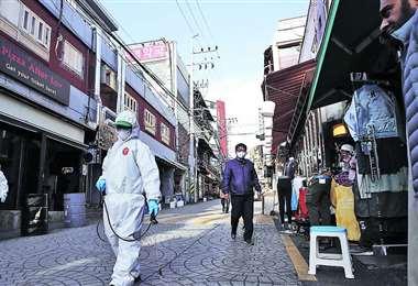 Funcionarios sanitarios desinfectan una calle del distrito Itaewon, en Seúl. Foto Internet