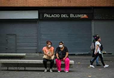 Personas usan máscaras faciales mientras descansan en el bulevar Sabana Grande, en Caracas en medio del nuevo brote de coronavirus (COVID-19).Foto: AFP
