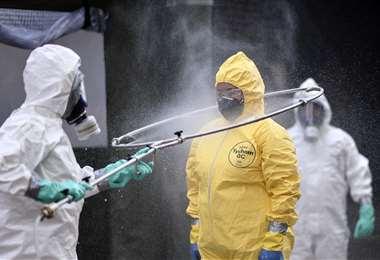 Miembros de Defensa Civil se desinfectan mutuamente luego de limpiar una terminal en Belo Horizonte. Foto AFP