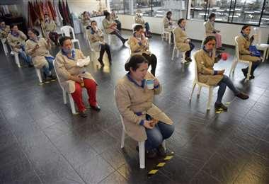 Empleados de una fábrica de artículos de cuero toman su refrigerio manteniendo el distanciamiento social en Bogotá. Foto AFP