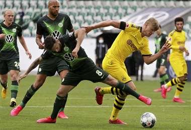 Erling Braut Haaland, del Borussia Dortmund, escapa a la marca de Renato Steffen, del Wolfsburg. Foto: AFP
