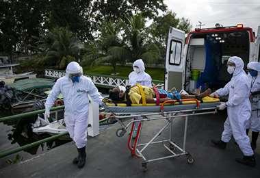 Un enfermo de coronavirus es llevado a un bote ambulancia en la región de Pará, en Brasil. Foto AFP
