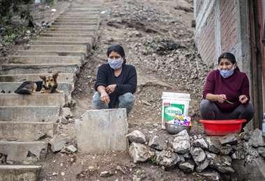 Dos mujeres esperan en un comedor comunitario de la zona de Pamplona Alto, al sur de Lima. Foto AFP