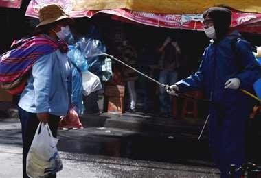 Una mujer se desinfecta en una de las calles de La Paz