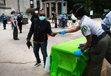 Reparten mascarillas gratis en un parque de Nueva York. Foto AFP