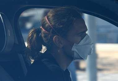 El delantero francés Antoine Griezmann llegó en su vehículo y con la mascarilla puesta. Foto (AFP)