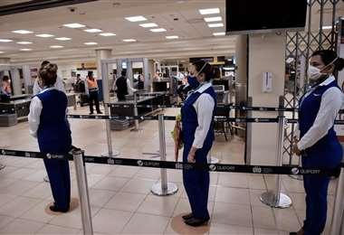 Personal de una aerolínea espera a pasajeros en el aeropuerto de Quito. Foto AFP