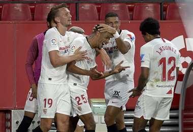 El brasileño Fernando (25) es felicitado por sus compañeros tras marcar el segundo gol del Sevilla. Foto: AFP