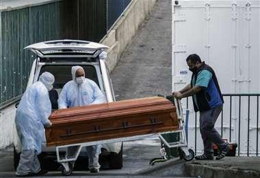 Empleados de una funeraria de Valparaíso sacan un ataúd con una víctima de Covid-19. Foto AFP