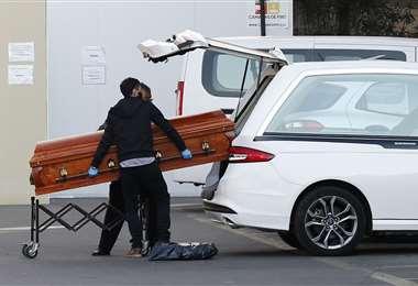 Empleados de una funeraria sacan el ataúd con un fallecido por coronavirus del hospital San José de Santiago. Foto AFP