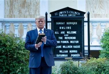 Trump con una Biblia afeura de la iglesia de San Juan, al frente de la Casa Blanca. Foto AFP