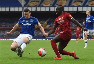Una de las figuras del Liverpool, Sadio Mane (dcha.), intenta eludir la marca del defensor del Everton Seamus Coleman. Foto: AFP