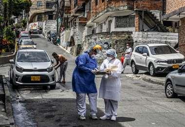 Miembros de una brigada médica realizan un rastrillaje en Medellín. Foto AFP