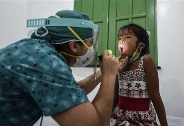 Un médico revisa a una niña indígena en Tabatinga, estado de Amazonas. Foto AFP