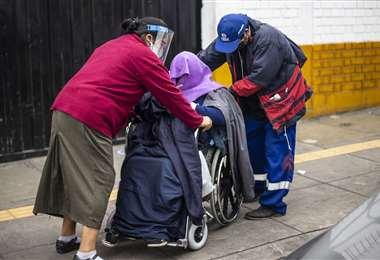 Familiares ayudan a una señora en silla de ruedas enferma de Covid-19 fuera de un hospital de Lima. Foto AFP