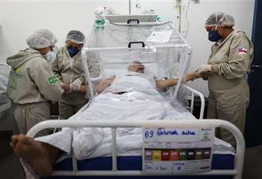 Paramédicos ayudan a un enfermo de Covid-19 en el hospital de Manaos. Foto AFP