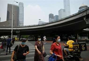 Peatones cruzan una calle de Pekín. Foto AFP