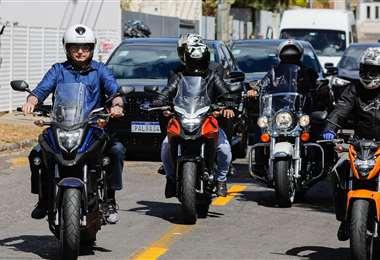 Bolsonaro (izq.) paseando en moto en Brasilia. Foto AFP