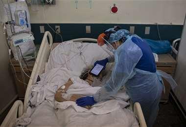 La doctora López sostiene un iPad para que un paciente terminal escuche un mensaje de despedida de sus familiares. Foto AFP