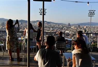 Gente en un bar con terraza con vista a la Sagrada Familia en Barcelona. Foto AFP