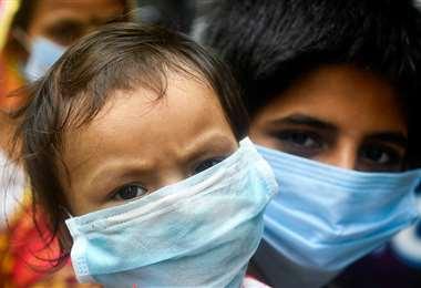 Niños usando el barbijo como método de protección al Covid-19 (AFP)