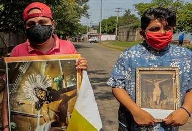 Católicos sostienen cuadros de una imagen que fue dañada por un incendio en la Catedral de Managua. Foto AFP
