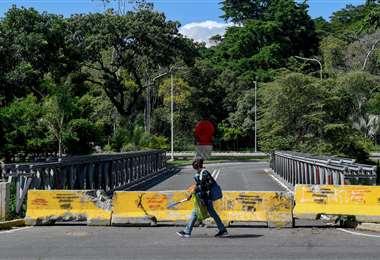 Un peatón pasa junto a una barricada colocada en un puente al sur de Caracas. Foto AFP