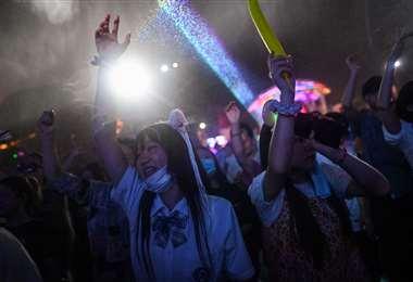 Jóvenes se divierten en una disco de Wuhan. Foto AFP