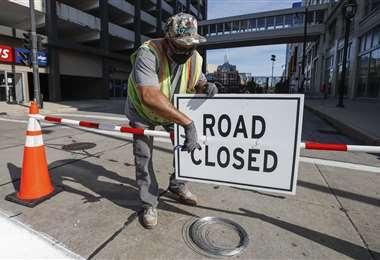 Un trabajador coloca un letrero de vía cerrada fuera del Wisconsin Center antes de la Convención Nacional Demócrata en Milwaukee, Wisconsin. Foto AFP
