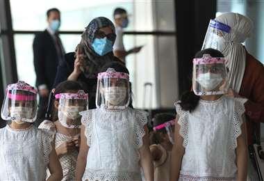 Una familia iraquí con máscaras protectoras camina en la sala de salidas del aeropuerto internacional de Bagdad luego de su reapertura. Foto AFP