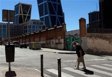 Un anciano con mascarilla camina por Madrid, con la Puerta de Europa (Torres Kio) al fondo. Foto AFP
