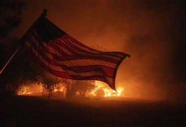 Una bandera estadounidense ondea en el viento frente a una casa en llamas en Vacaville, California, durante el incendio del Complejo Relámpago. Foto. AFP