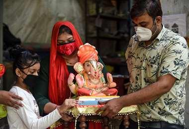 Devotos llevan la imagen de la deidad hindú con cabeza de elefante Ganesha. Foto AFP