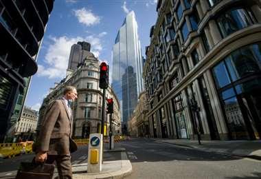 Un hombre cruza una calle desierta en la City londinense. Foto AFP