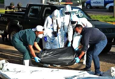 Policías recogen un cuerpo de una calle de Tegucigalpa. Foto AFP