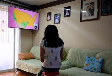Una alumna atenta a sus clases por TV. Foto AFP