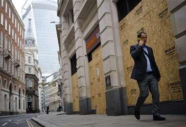 Un hombre camina por una calle desierta del centro de Londres. Foto AFP