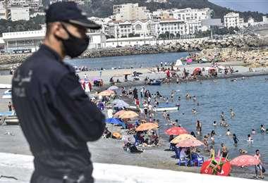 Un policía vigila una playa de Argel, donde se han levantado restricciones. Foto AFP