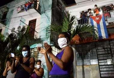 Vecinos aplauden en reconocimiento a los médicos y enfermeras que luchan contra el nuevo coronavirus en La Habana. Foto AFP.