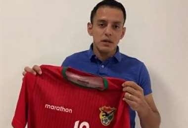 Jhasmani Campos muestra la camiseta que donará. Foto: internet