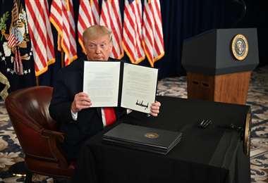 El presidente Donald Trump firma órdenes ejecutivas que extienden el alivio económico por el coronavirus. Foto AFP