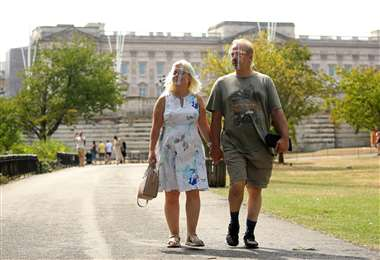 Una pareja con protectores faciales camina frente al Palacio de Buckingham en St James Park. Foto AFP