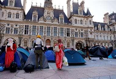 Migrantes son sacados por policías hoy martes del frente de la Alcaldía de París. Foto AFP