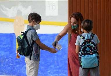 Una profesora desinfecta las manos al inicio de clases en una escuela de Sevilla. Foto AFP
