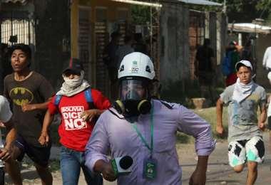 Grupos de manifestantes persiguen a los periodistas.  Foto: Fuad Landívar