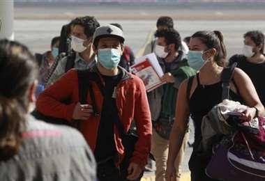 Varias personas caminan por una calle de Santiago. Foto AFP