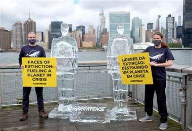 Gente de Greenpeace junto a las esculturas de hielo. Foto AFP
