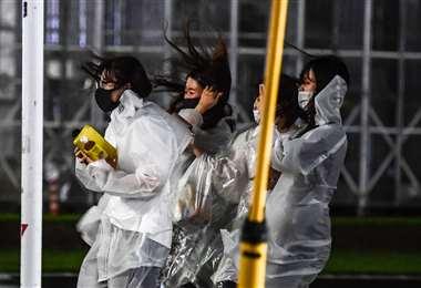 Mujeres caminan bajo la lluvia cuando el tifón Haishen golpea Kagoshima. Foto AFP