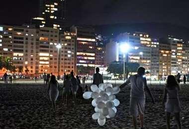 Un puñado de personas celebran en la playa de Copacabana I AFP.